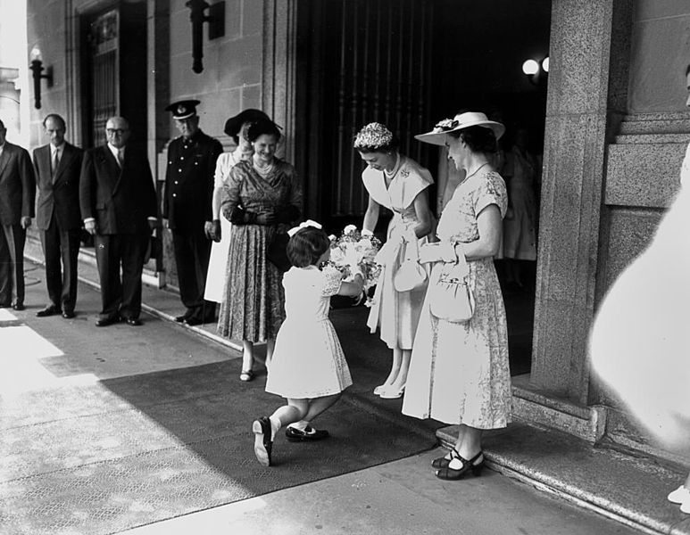 A young girl curtsies as she presents a bouquet of flowers to Queen Elizabeth II outside Brisbane City Hall in March 1954.