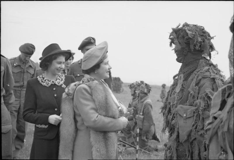 The Queen and Princess Elizabeth talk to a camouflaged sniper during a tour of Airborne forces, May 19, 1944, just weeks before D-Day.