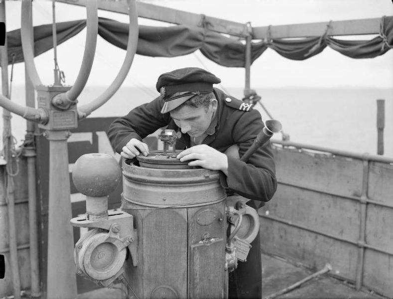 A Navy Sailor taking a compass reading whilst the ship was in convoy, during the Second World War.