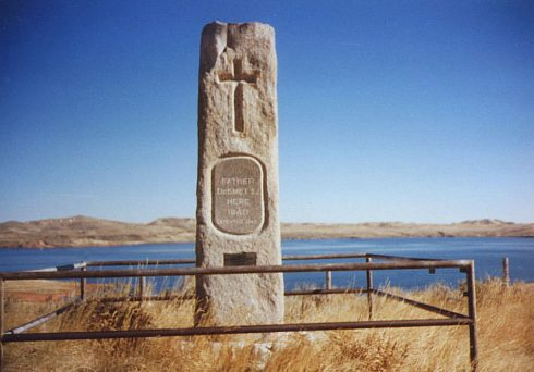 "Father De Smet Monument at Lake Desmet between Buffalo and Sheridan Wyoming. Lake Desmet, pictured behind the monument, is a 3600 acre natural lake. Fr. De Smet, after whom the lake is named, described the lake in a letter dated August 24, 1851: ""On the 23rd we left Tongue River. For ten hours we marched over mountain and valley, following the course of one of its tributaries, making, however, only about twenty-five miles. On the day following we crossed a chain of lofty mountains to attain the Lower Piney Fork, nearly twenty miles distant. We arrived quite unexpectedly on the borders of a lovely little lake about six miles long, and my traveling companions gave it my name. There our hunters killed several wild ducks."""