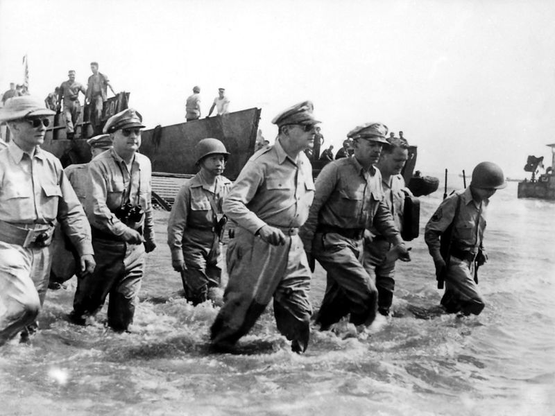 General Douglas MacArthur, accompanied by Lieutenant Generals George C. Kenney and Richard K. Sutherland and Major General Verne D. Mudge, wades ashore during initial landings at Leyte Island, Philippine on October 20, 1944.