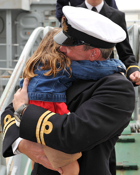 A Royal Navy officer hugs his daughter on return from a long deployment abroad. Photo by Photo: LA(Phot) Dave Jenkins/MOD