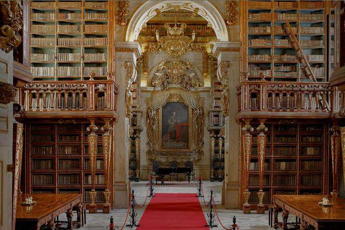 Interior of the Joanina Library of the University of Coimbra, Portugal. The library was built in the 18th century and named after King John V of Portugal, whose painting is in the middle. Photo by Wirdung.