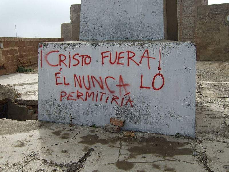 This graffiti is at the base of a statue of the Sacred Heart at the Castle of Monzon, Aragon, Spain. Photo by Ecelan.