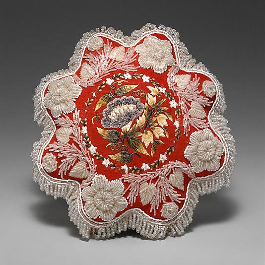 A Huron beaded pincushion, with moosehair embroidery in the center. Circa 1860.