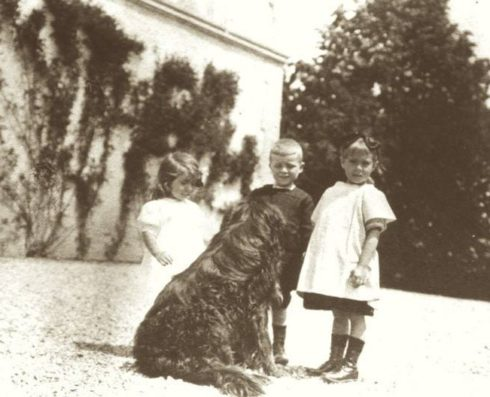 Anne, aged about six, with Magdeleine, Jacques and Rajah, the family dog .