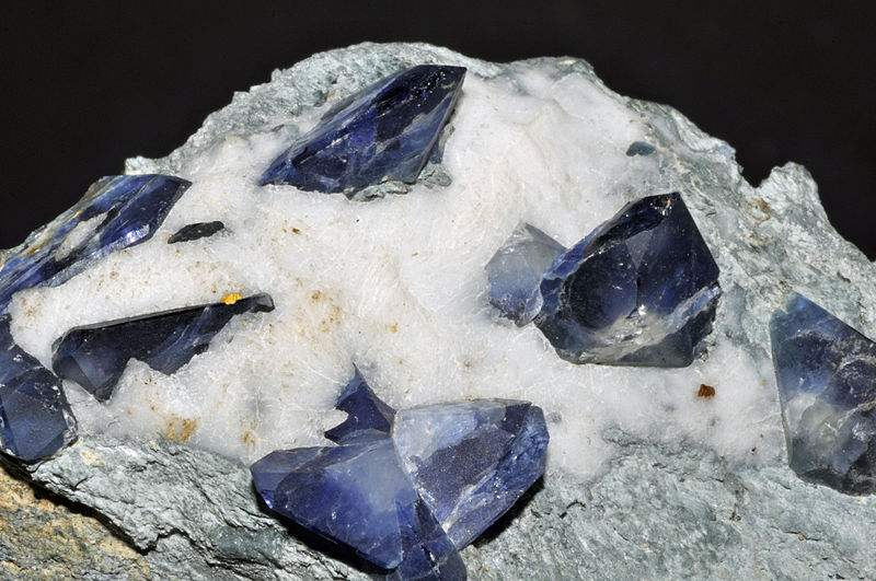 Crystals of benitoite, which is a rare blue barium titanium silicate mineral, found in hydrothermally altered serpentinite. Benitoite fluoresces under short wave ultraviolet light, appearing bright blue to bluish white in color.