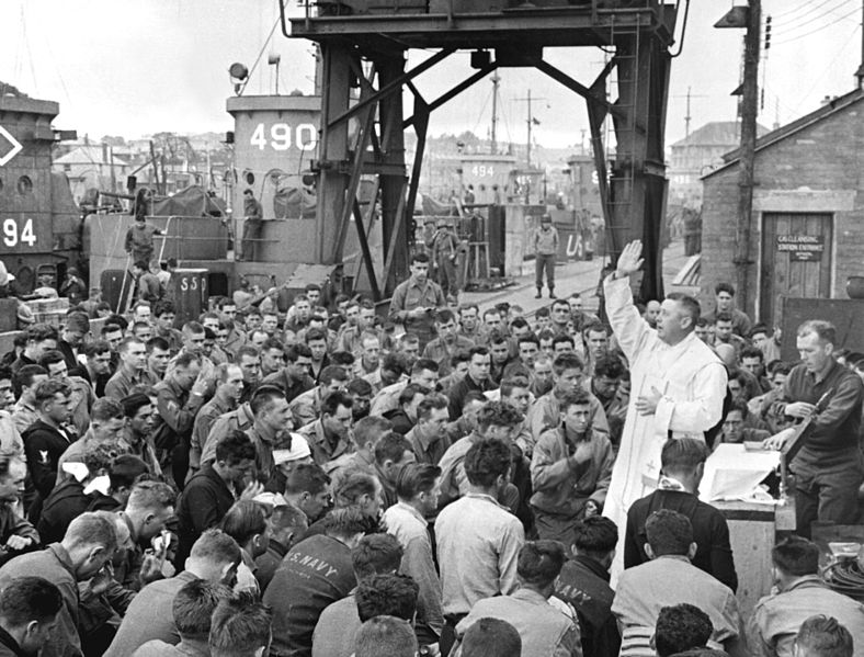 Father (Major) Edward J. Waters, just concluding Mass on a pier for members of the first assault troops thrown against Hitler's forces on the continent.